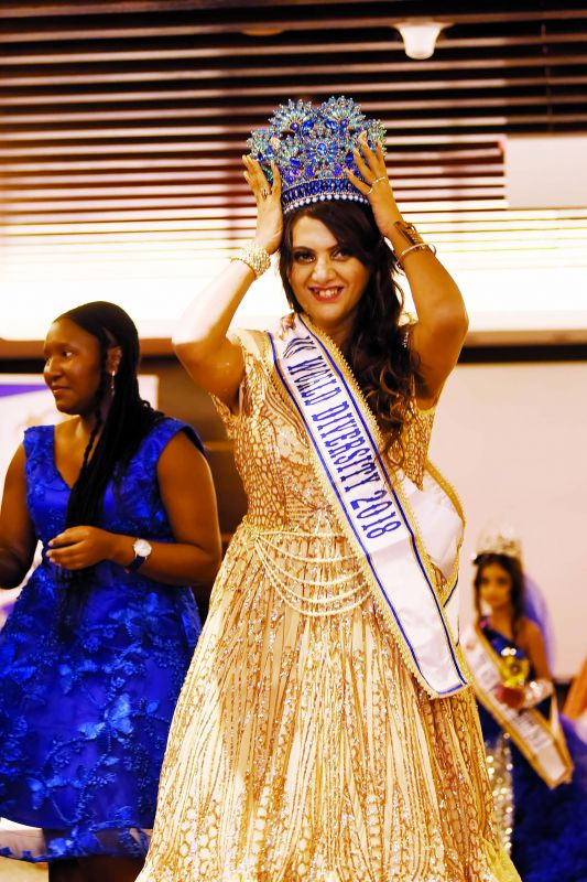 Aizya holds her crown in place