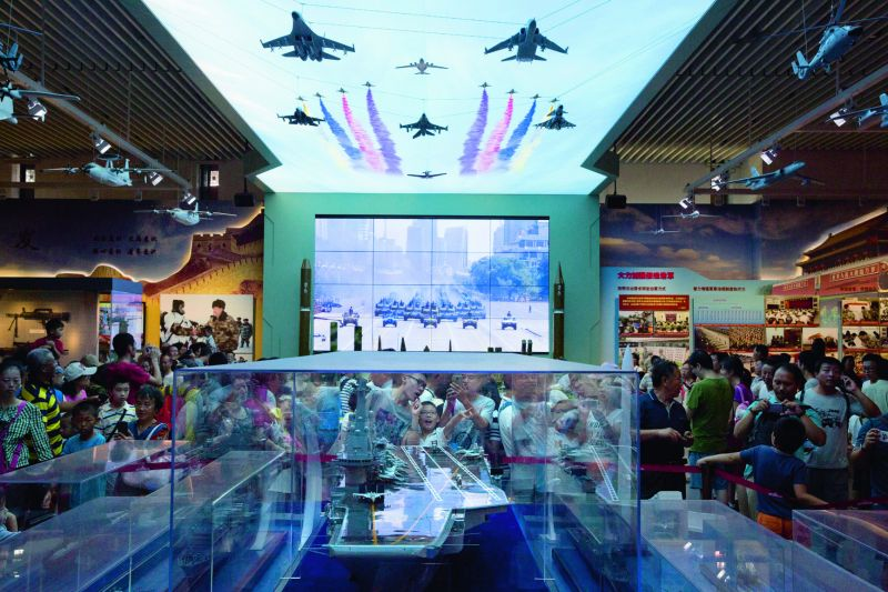 Visitors look at a scale model of a Chinese aircraft carrier during an exhibition at the military museum in Beijing.