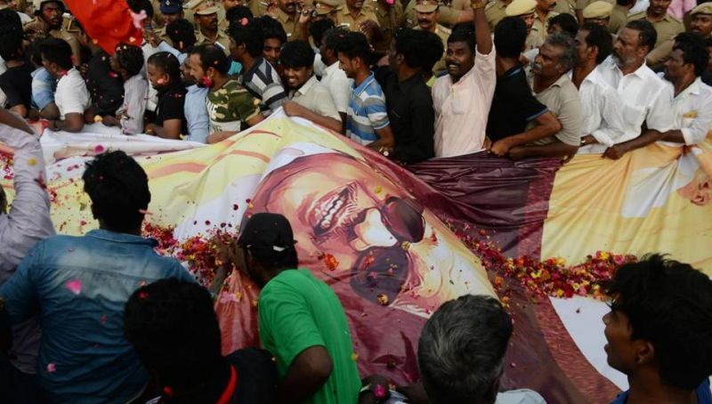 Supporters carry a large banner of the DMK patriarch during the funeral procession in Chennai. (Photo: AFP)