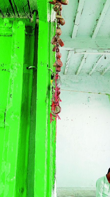 Threads and locks, put up by devotees, hang from an iron chain on the doorway to the shrine.