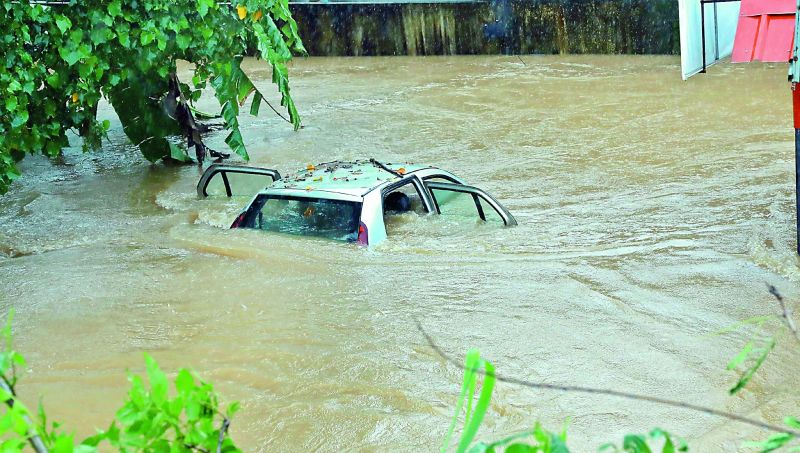 A fully-submerged car at Edappally in Kochi on Thursday as rains battered the city for the second day in succession. (Image: PTI, ARUN CHANDRABOSE)