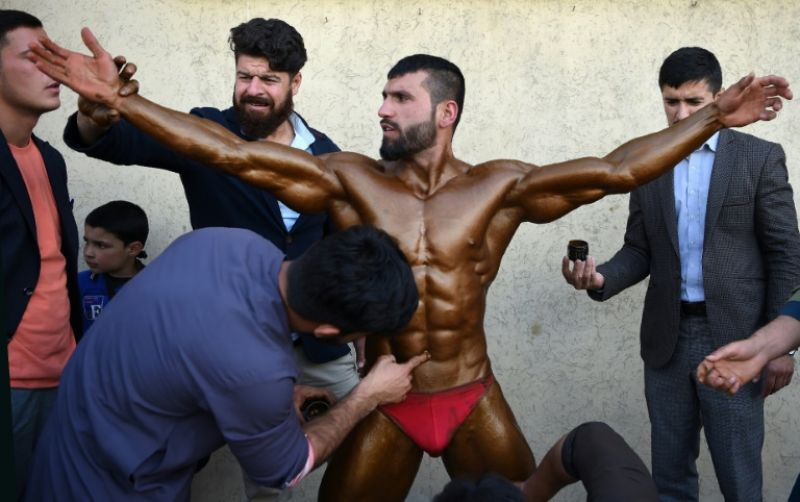 Bodybuilder Hares Mohammadi, 25, being covered in fake tan during a contest in Kabul. (Photo: AFP)