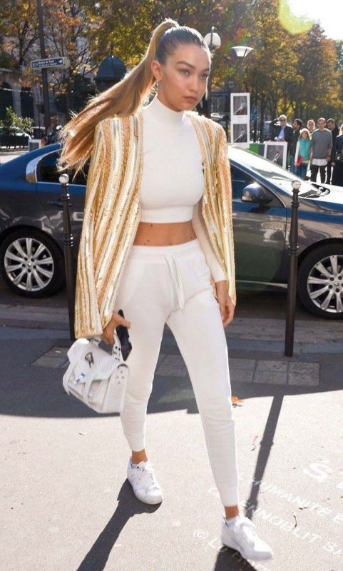 Gigi Hadid wears plain white pants that go well with any floral top while travelling.