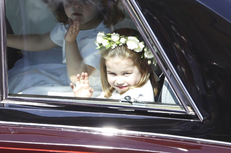 Princess Charlotte waves as she rides in a car to the wedding ceremony of Prince Harry and Meghan Markle at St. George's Chapel in Windsor Castle in Windsor. (Photo: AP)