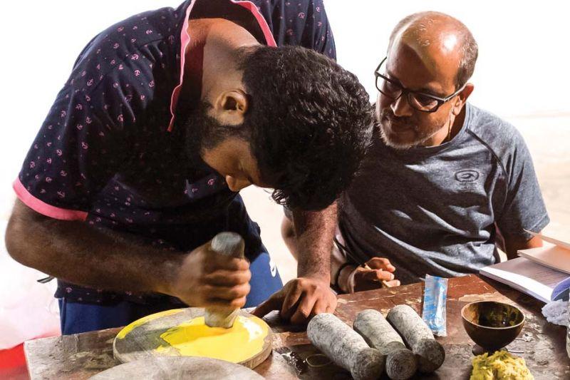 Artist P.K. Sadanandan (right) preparing colours for his work