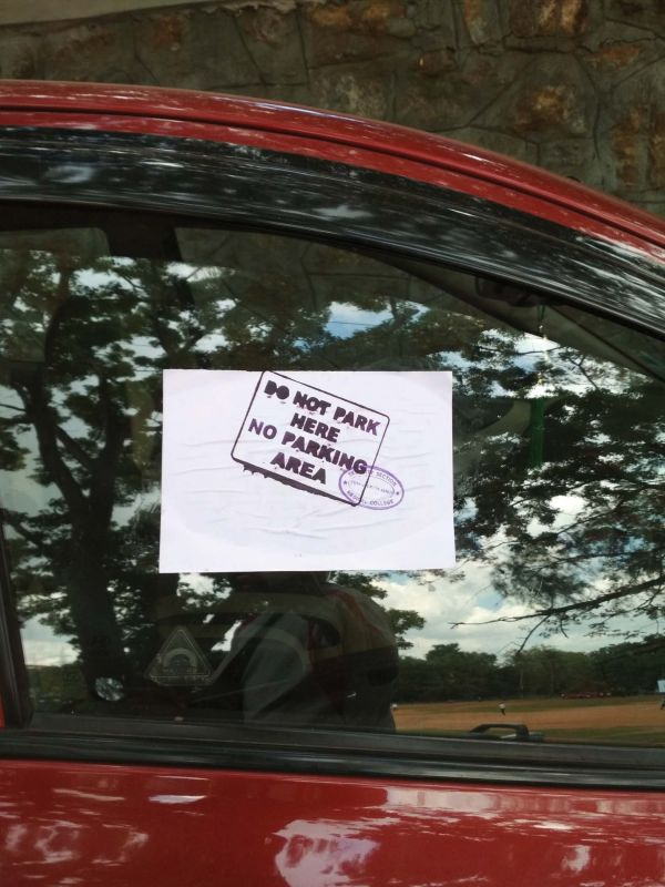 A sticker pasted on a car parked on the no-parking zone enroute Priyadarshini Institute of Paramedical Sciences.