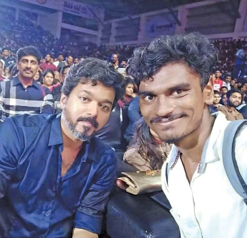 Vijay poses for a selfie with a lucky fan at the audio launch