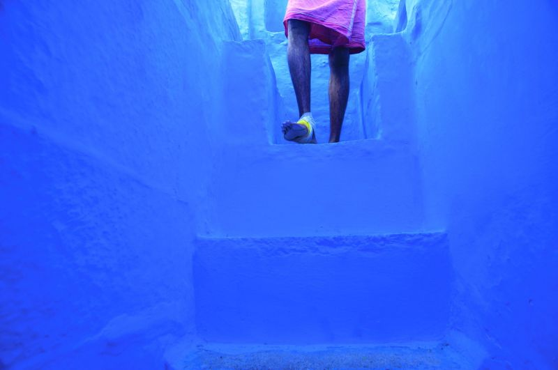 A man descends the steps in his home during the morning of Diwali in Jodhpur, the Blue City, India.