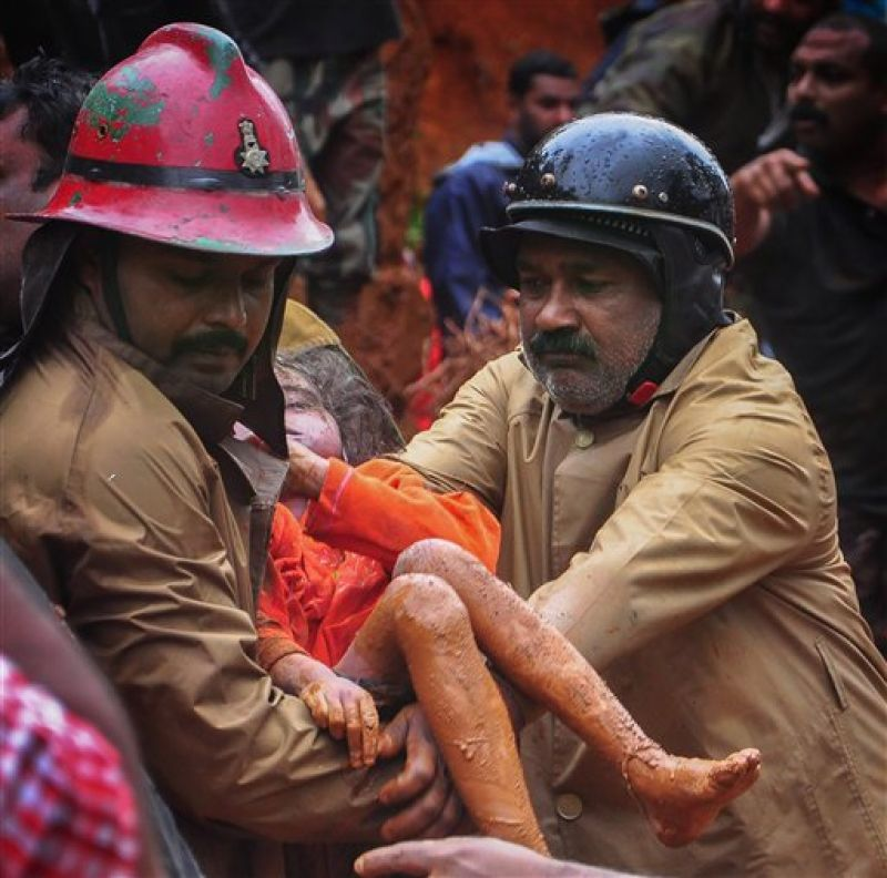 Fire Services personnel rescue a child following a landslide, triggered by heavy rains, in Idukki, Kerala. (Photo: PTI)