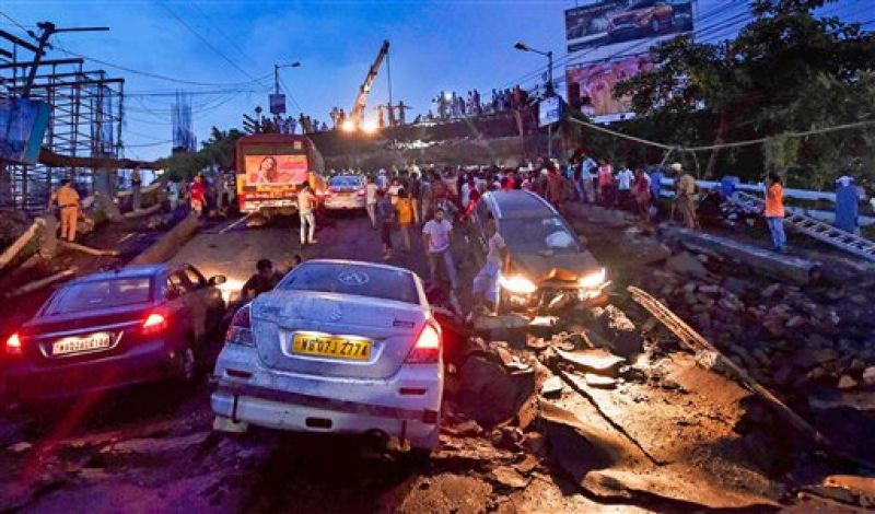 Rescue workers remove vehicles and debris from the collapsed Majerhat bridge, in Kolkata, Tuesday. (Photo: PTI)