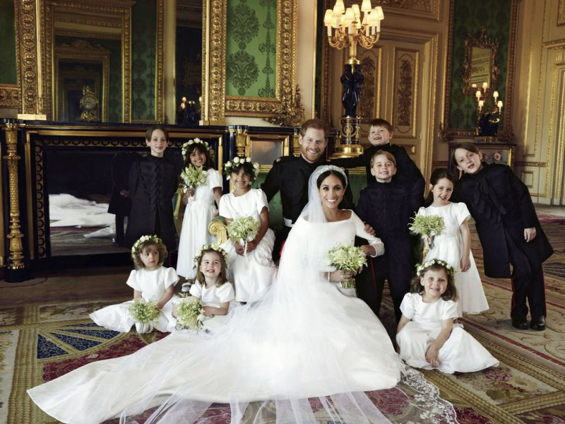 In this photo released by Kensington Palace on Monday May 21, 2018, shows an official wedding photo of Britain's Prince Harry and Meghan Markle, center, in Windsor Castle, Windsor, England, Saturday May 19, 2018. Others in photo from left, back row, Brian Mulroney, Remi Litt, Rylan Litt, Jasper Dyer, Prince George, Ivy Mulroney, John Mulroney; front row, Zalie Warren, Princess Charlotte, Florence van Cutsem.
