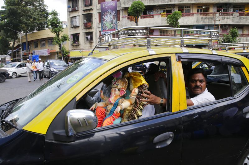 Devotees carry home an idol of elephant-headed Hindu god Ganesha in a taxi for worship during Ganesh Chaturthi festival celebrations in Mumbai. (Photo: AP)