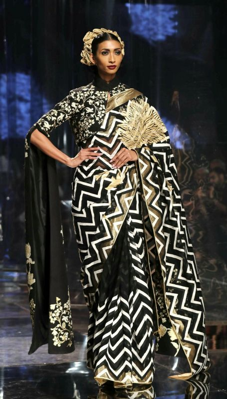 A beautiful black, white and gold sari in a geometric pattern teamed with a floral blouse with trendy floor-length sleeves. (Photo: AP)