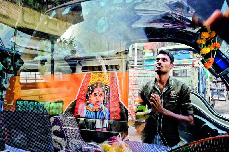 A man prays to the Goddess on the streets of Lucknow, with the reflection of it falling on the glass of a car parked in front.