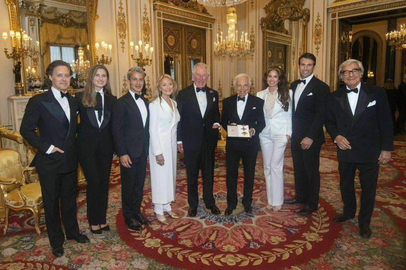 The Prince of Wales, center, presents designer Ralph Lauren, fourth right, with his honorary KBE. (Photo: AP)