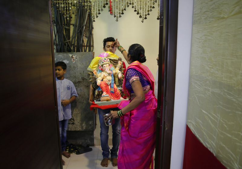Devotees offer prayers before entering their homes with an idol of elephant-headed Hindu God Ganesha during Ganesh Chaturthi festival celebrations in Mumbai. (Photo: AP)