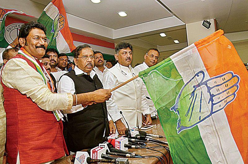 Hosapete MLA Anand Singh  waves the Congress flag after he was inducted into the party at a programme at the KPCC office in Bengaluru on Wednesday.