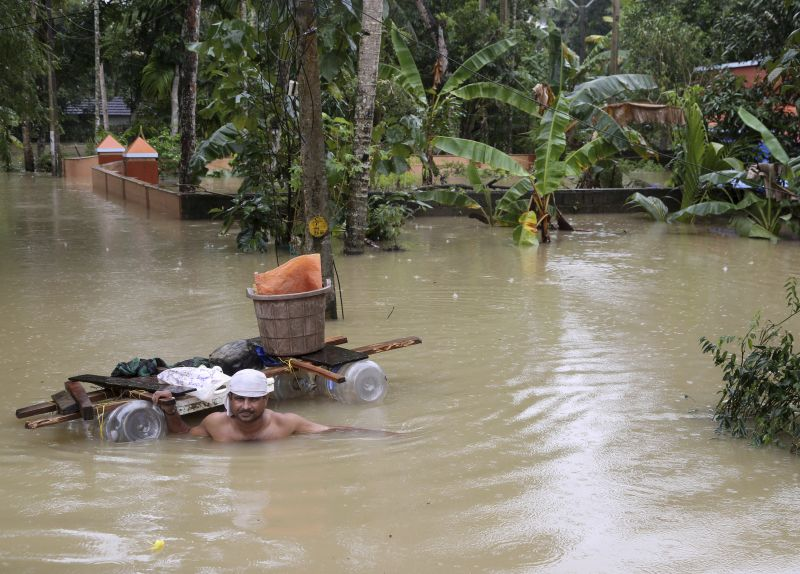 A stranded man wades through flood waters with a makeshift raft in Chengannur. (Photo: PTI)