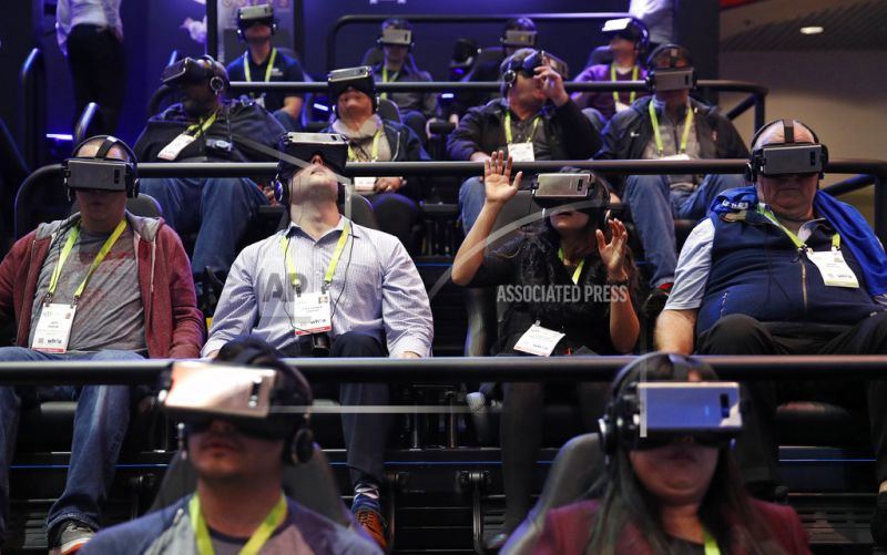 People look through Samsung Gear VR virtual reality goggles at the Samsung booth.