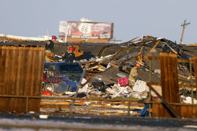 Workers look through tornado damage near the American Budget Value Inn in El Reno, Okla., Sunday, May 26, 2019. The deadly tornado leveled a motel and tore through the mobile home park near Oklahoma City overnight. (Bryan Terry/The Oklahoman via AP)