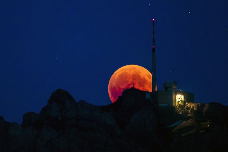 The moon turns red during a total lunar eclipse, behind the Saentis in Luzern, Switzerland, on Friday. (Photo: AP)