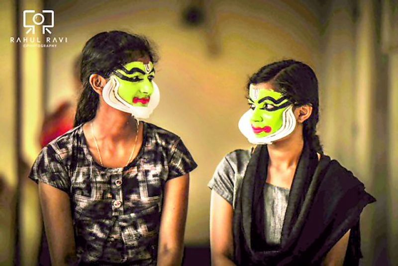 Young Kathakali artistes exchange glances during their makeup session.
