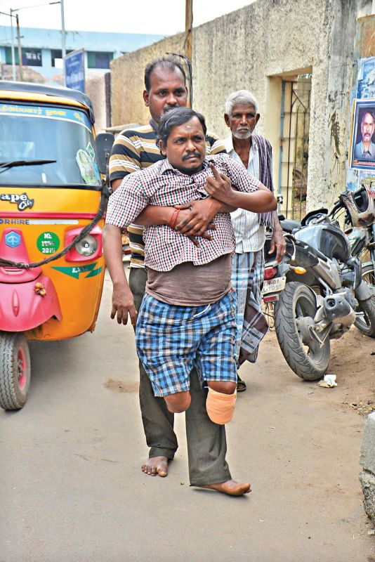 A man assists a physically challenged voter at Cheriyan Nagar, on Thursday. (Photo: DC)