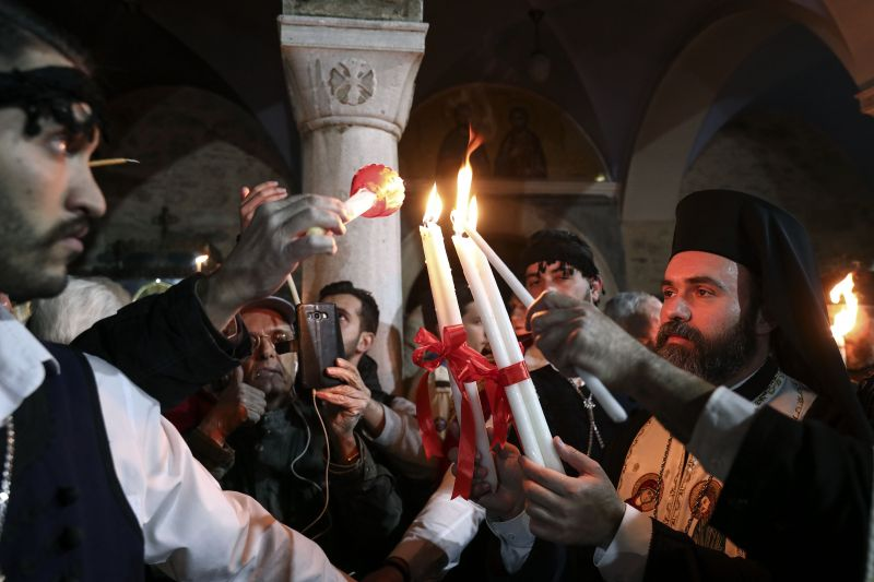 A Greek Orthodox priest lights candles of the faithful with Holy Fire brought from Jerusalem outside a church in Athens, on Saturday, April 7, 2018.Across the world, Orthodox Christians are celebrating Easter, commemorating the day followers believe that Jesus was resurrected more than 2,000 years ago. (Photo: AP)