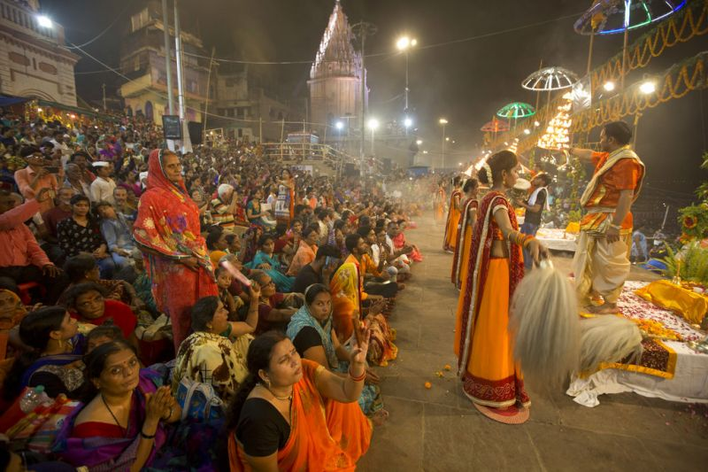A Hindu priest prays as women devotees stand during the Ganga Dussehra festival on the banks of the River Ganges in Varanasi, India, Thursday, May 24, 2018. Hindus across the country celebrate Ganga Dussehra by worshiping the River Ganges, which is considered the most sacred and the holiest river for Hindus.  (AP)