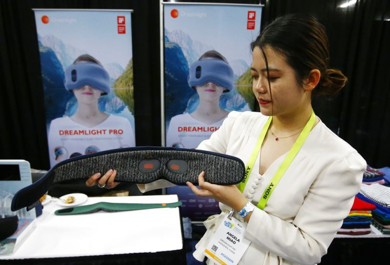 Angela Miao, of Dreamlight, demonstrates their new sleep mask Dreamlight Pro that uses light, sound and genetics so you fall asleep faster and wake up with more energy according to the company, at the CES Unveiled at CES International Sunday, Jan. 6, 2019, in Las Vegas. (AP Photo/Ross D. Franklin)