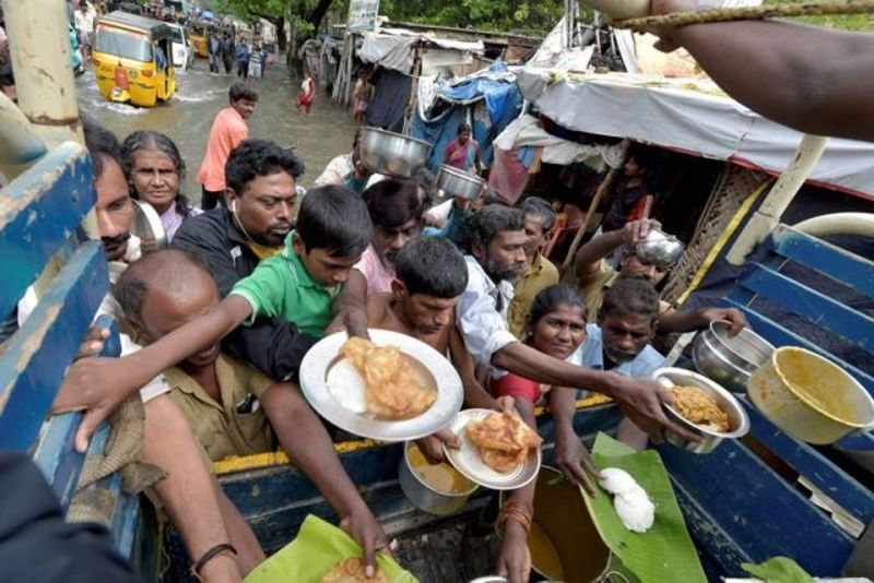 Volunteers distribute food to residents in flooded areas. (Photo: PTI)
