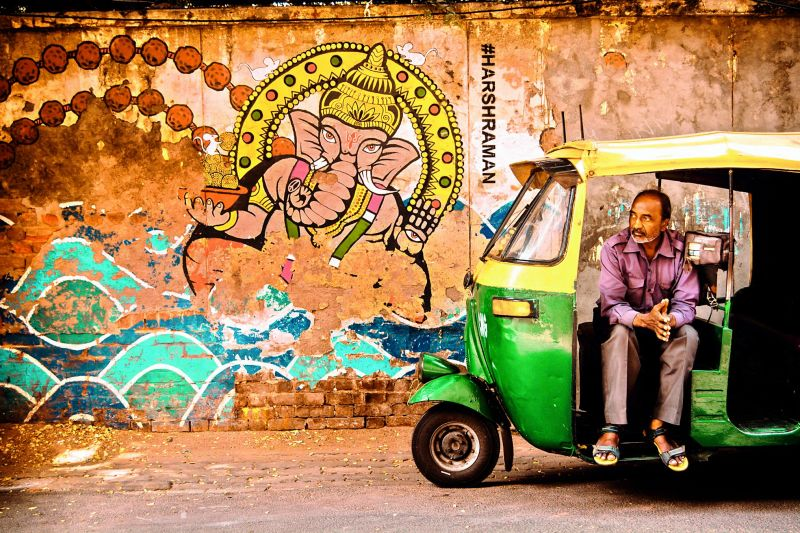 An auto-rickshaw driver awaits a ride.