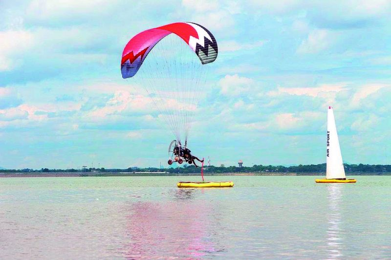 P. R. Singh refuelling his Paramotor on the eve of the World Paramotor Championship (WPC) in 2018 in Thailand and (right) Singh competing during a Slalom event on water during WPC.