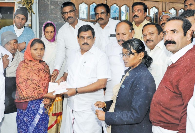 K.Radhakrishnan,  minister for animal husbandry, hands over the compensation to the member of  a flood affected family at Kuruthukuli village near Ooty on Sunday.  (Photo: DC)