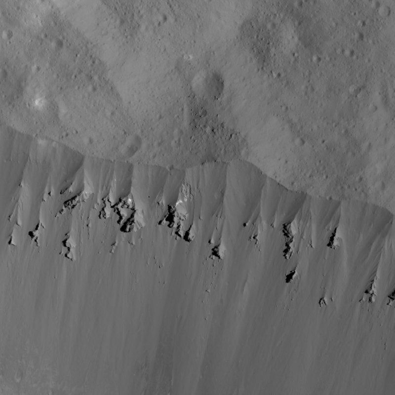 This image showing landslides along Occator Crater's rim was obtained by NASA's Dawn spacecraft on June 9, 2018 from an altitude of about 27 miles. Dawn has been orbiting Ceres since 2015, after first exploring the asteroid Vesta. They're located in the asteroid belt between the orbits of Mars and Jupiter. (NASA via AP)