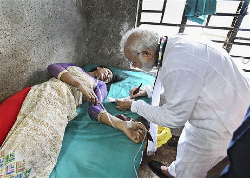 Prime Minister Narendra Modi gives autograph to Rita Mudi in hospital. (Photo: PTI)