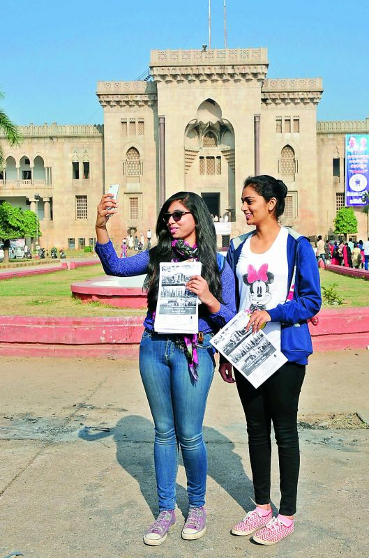 Youngsters clicking selfies in front of Arts College building.