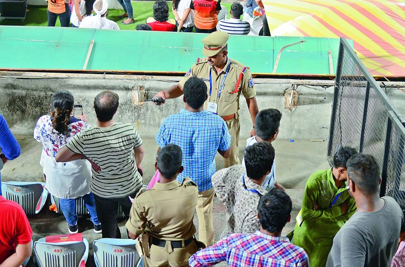 A policeman at the South Pavilion West seating orders spectators to clear the place as they watch the post-match ceremony at the RGICS in Hyderabad on Saturday.