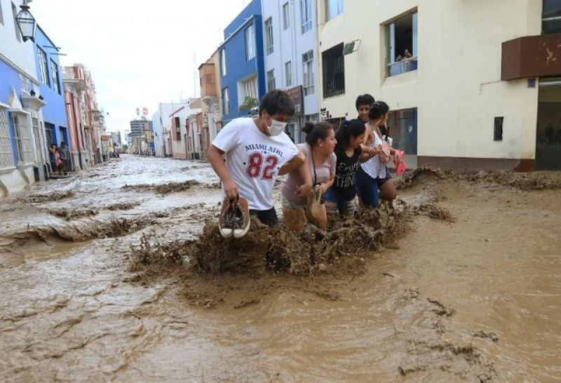 Residents wade through the water as a flash flood hits the city of Trujillo on March 18, 2017, bringing mud and debris. (Photo: AFP)