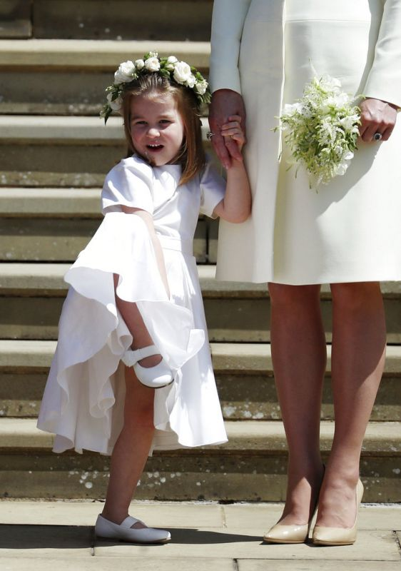 The three-year-old can be seen in good spirits following the royal wedding, as she stood on the church's steps and waved while holding Kate's hand. (Photo: AP)