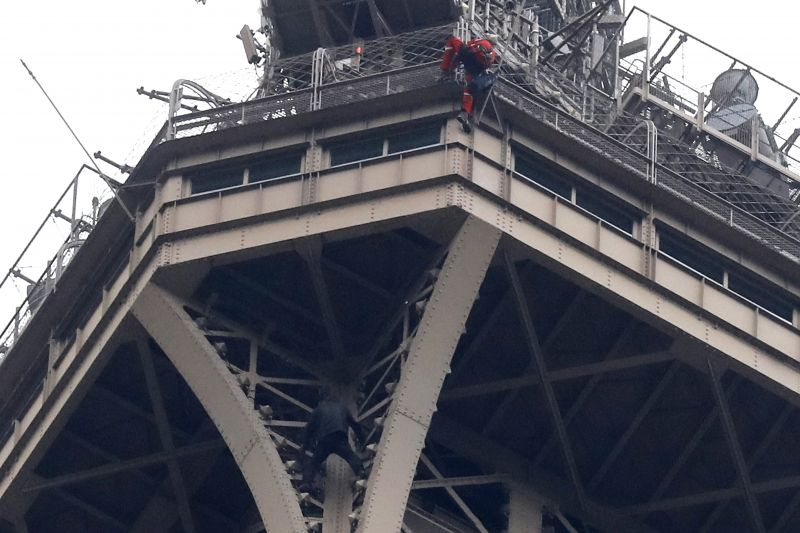 A rescue worker, top in red, climbs the Eiffel Tower while a climber is seen below him between two iron columns Monday, May 20, 2019 in Paris. The Eiffel Tower has been closed to visitors after a person has tried to scale it. (AP Photo/Michel Euler)