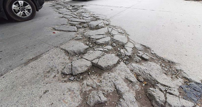Potholes and cracks on a whitetopped road in Vasanth Nagar