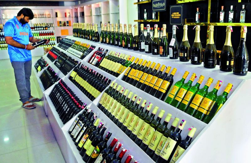 A customer checks out a bottle of wine at a liquor mart in the city that opened recently.