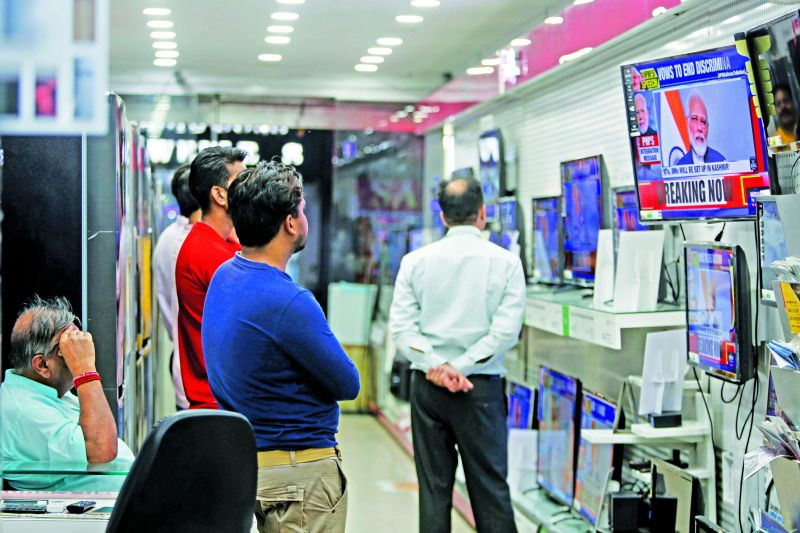 People watch Prime Minister Narendra Modi address the nation in a televised speech, at an electronics store in Jammu, India, Thursday. (Photo: AP)