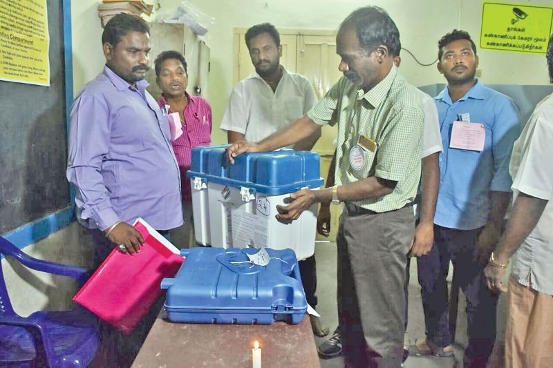 Election officers secure electronic voting machines after polling ended at a booth in Nethaji Nagar. (Photo: DC)