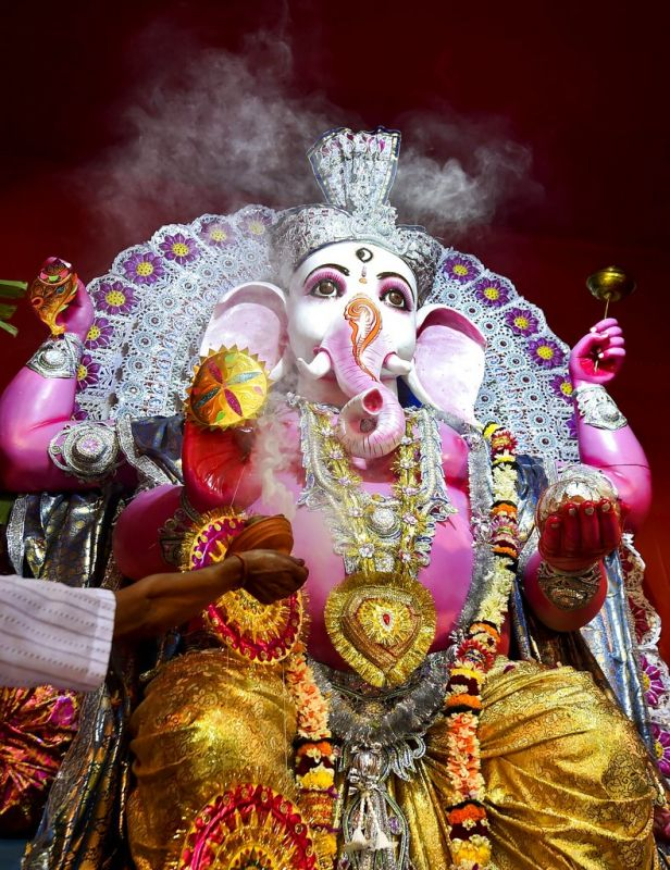 A priest offers prayers to Lord Ganesh at a community puja pandal on the occasion of Ganesh Chaturthi in Kolkata. (Photo: PTI)