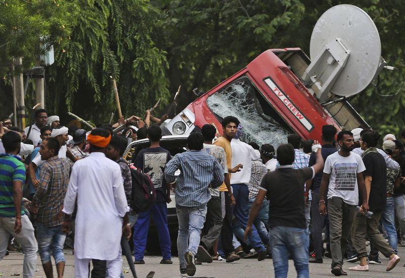 Dera Sacha Sauda sect members overturn an OB van on the streets of Panchkula on Friday. (Photo: PTI)
