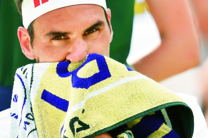 Roger Federer wipes his face during his Wimbledon men's singles first round match against South Africa's Lloyd Harris. (Photo: AFP)