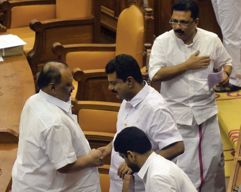 Transport Minister Thomas Chandy greets Nilambur MLA P.V. Anwar after the report was presented. Both members are embroiled in encroachment controversy. Minister for Local Self-Governments K.T. Jaleel looks on. On extreme left, Opposition leader Ramesh Chennithala is seen making a point before the report presentation.