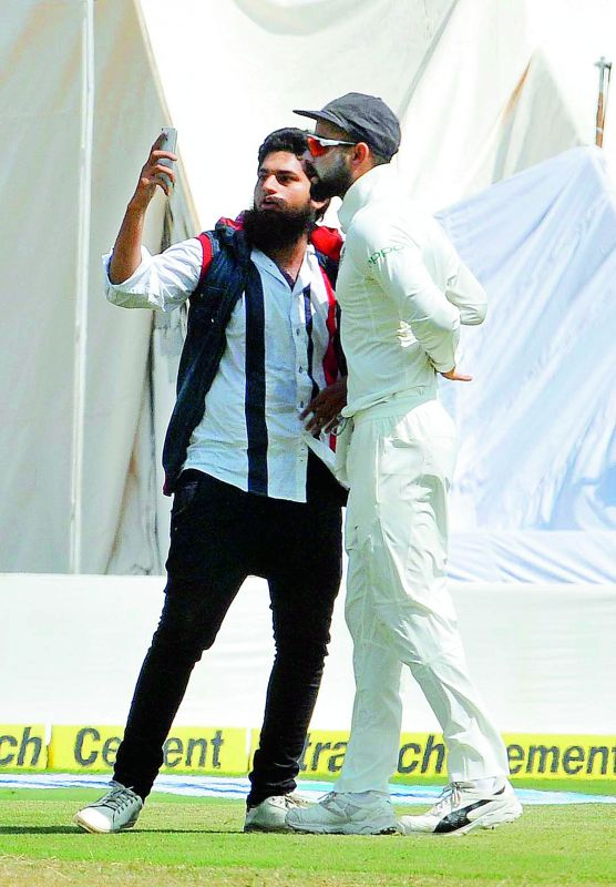 Mohammed Khan takes a selfie with Virat Kohli after running on to the ground on Friday.— P. Surendra